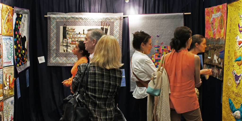 People viewing an exhibition of Mexican quilts